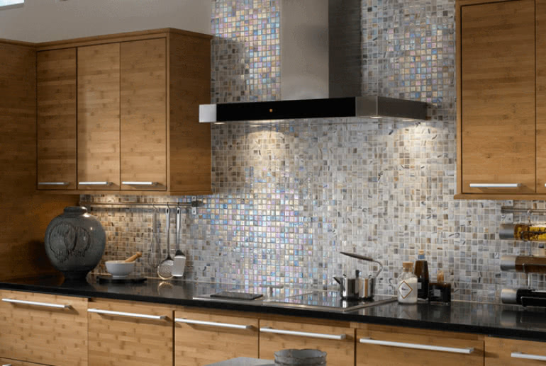 Alyse Edward Haute Glass Opaque tile in Tres Leches is used as a backsplash to add a pop of glam to this contemporary kitchen. Available at Home Carpet One.